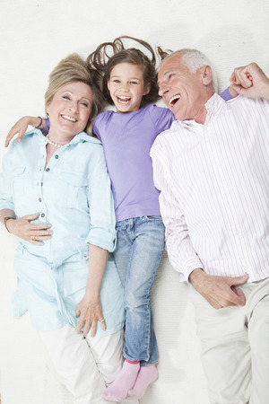Granddaughter (6-7) Lying With Grandparents,Smiling LANG_EVOIMAGES