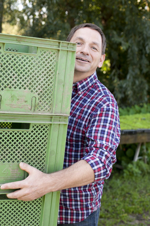 Germany,Saxony,Mature Man Carrying Crate,Portrait