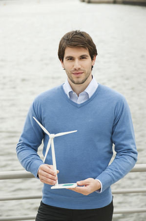 Germany,Hamburg,Businessman Holding Wind Turbine,Portrait