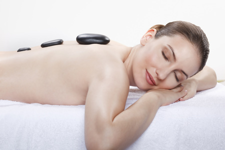 lastone therapy: Woman Having A Hot Stone Treatment,Smiling,Eyes Closed LANG_EVOIMAGES