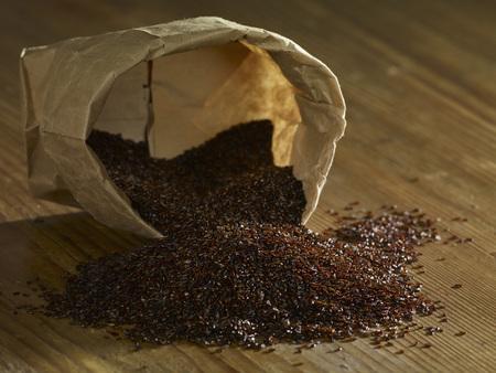 Psyllium Seeds Spilling On Wooden Surface LANG_EVOIMAGES
