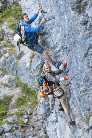 Austria,Steiermark,Ramsau,Silberkarklamm,Young Couple Climbing Rock