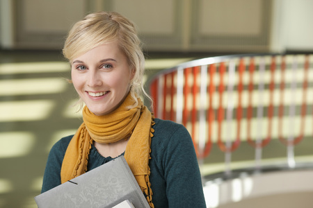 Germany,Leipzig,Young Woman Standing With Books In Hallway,Smiling,Portrait