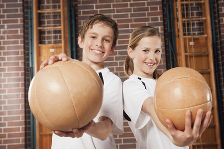 Germany,Emmering,Boy And Girl (12-13) Holding Ball And Smiling,Portrait
