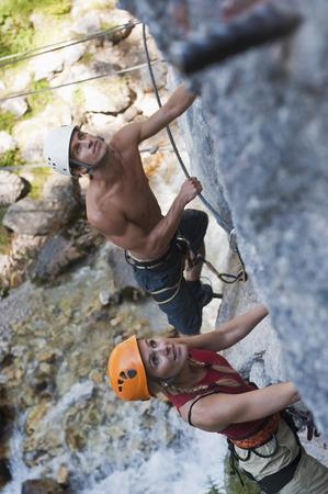 Austria,Steiermark,Ramsau,Silberkarklamm,Young Couple Climbing Rock,Looking Up