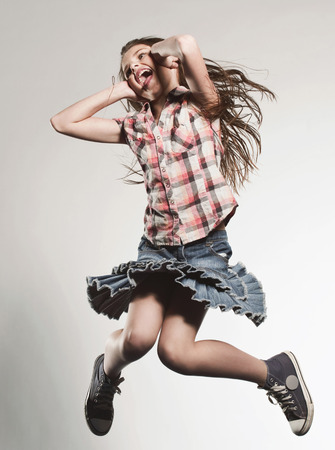 Girl (8-9) Jumping With Hands Covering Ears LANG_EVOIMAGES