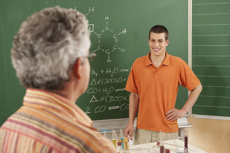 Germany,Emmering,Young Man Smiling With Teacher In Foreground LANG_EVOIMAGES