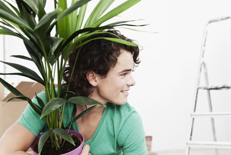 Germany,Cologne,Young Man Holding Pot Plant At Renovating Apartment