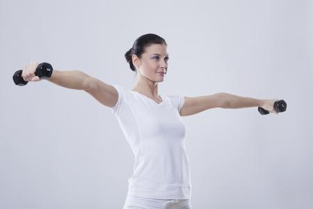 levantar peso: Mujer adulta media con Barbells contra el fondo blanco