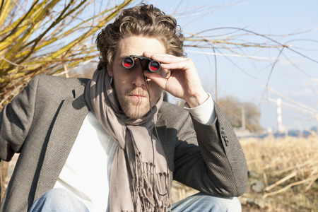 Germany,Hamburg,Man Looking Through Binoculars Near Elbe Riverside LANG_EVOIMAGES