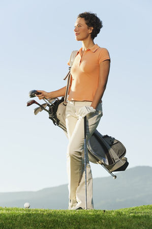Italy,Kastelruth,Mid Adult Woman With Golf Bag On Golf Course
