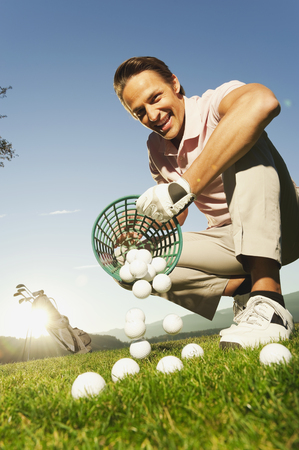 cowering: Italy,Kastelruth,Mid Adult Man Pouring Basket Of Golf Balls On Golf Course
