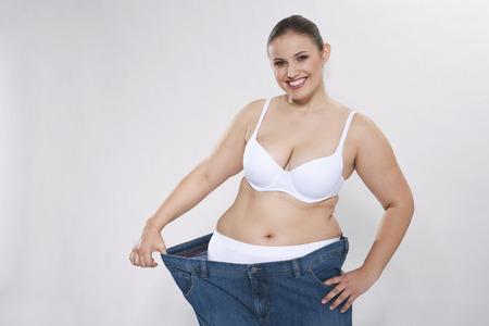 levantar peso: Mujer gordita joven con pantalón extragrande, retrato