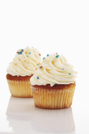Close Up Of Buttercream Vanilla Cupcake Against White Background