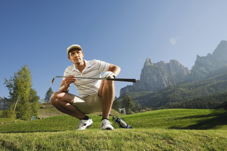 cowering: Italy,Kastelruth,Mid Adult Man On Golf Course