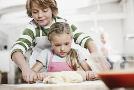 nudelholz: Germany,Cologne,Boy And Girl Rolling Dough,Mother In Background LANG_EVOIMAGES