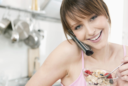Germany,Cologne,Woman Eating Fruit Muesli With On The Phone