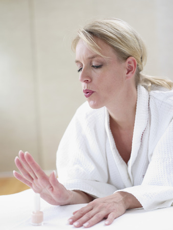 Mature Woman Blowing To Dry Nail Varnish