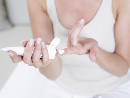 cremas faciales: Mujer madura apretando el tubo humectante en su dedo