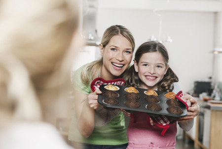 Germany,Cologne,Mother And Daughter Holding Cup Cakes In Baking Tray,Smiling