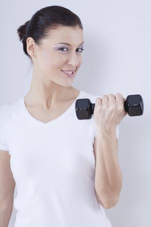 levantar peso: Ciérrese para arriba de la mediados de mujer adulta con los Barbells contra el fondo blanco, sonriendo, retrato