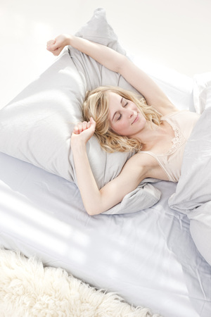 puños cerrados: Germany,Leipzig,Young Woman Stretching In Bed