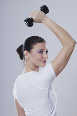 levantar peso: Mid Adult Woman With Barbells Against White Background,Smiling,Portrait