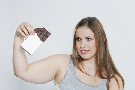 Young Chubby Woman With Chocolate Bar LANG_EVOIMAGES