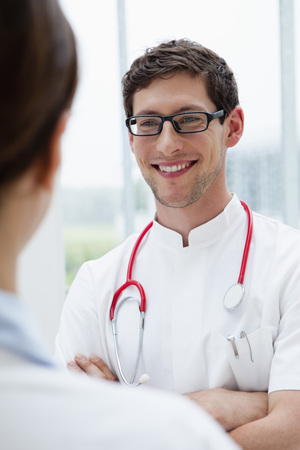 Germany,Bavaria,Diessen Am Ammersee,Two Young Doctors With Stethoscope Standing Face To Face,Smiling