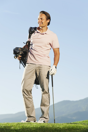 Italy,Kastelruth,Mid Adult Man With Golf Bag On Golf Course LANG_EVOIMAGES