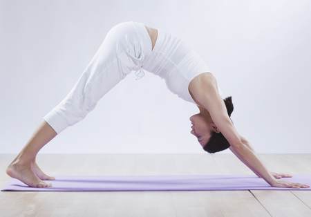 feet naked: Mid Adult Woman Doing Downward Facing Dog Position Against White Background