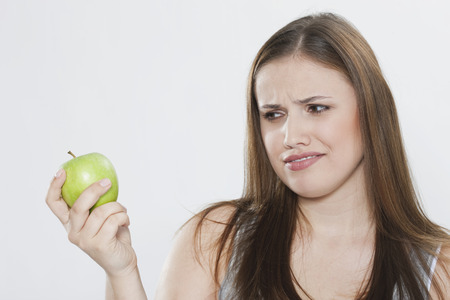 disgusted: Young Woman Looking At Green Apple