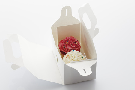 Close Up Of Strawberry And Vanilla Buttercream Cupcakes In Box Against White Background LANG_EVOIMAGES