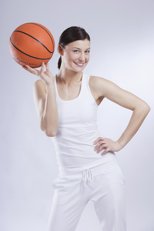 Mid Adult Woman With Basket Ball Against White Background,Smiling,Portrait LANG_EVOIMAGES