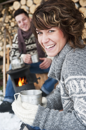 Austria,Salzburg Country,Flachau,Young Man And Woman Making Tea And Sitting Besides Stove In Winter LANG_EVOIMAGES
