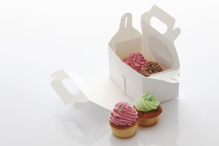 Close Up Of Strawberry,Chocolate And Woodruff Buttercream Cupcakes In Box Against White Background