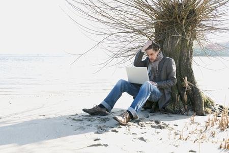 Germany,Hamburg,Man Sitting Beside Tree And Using Laptop Near Elbe Riverside