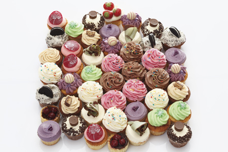 Variety Of Buttercream Cupcakes Against White Background