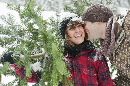 Austria,Salzburg Country,Flachau,Young Man And Woman Holding Christmas Tree LANG_EVOIMAGES