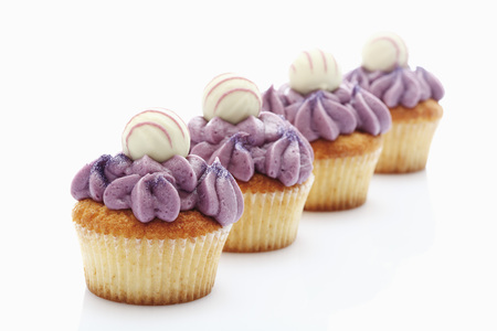 cup four: Close Up Of Buttercream Black Currant Cupcake With Chocolate Truffle Against White Background LANG_EVOIMAGES