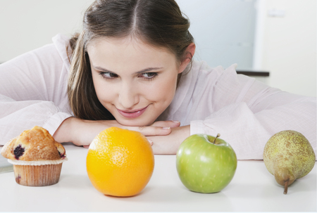 Germany,Cologne,Young Woman Is Confused Between Fruits And Sweets