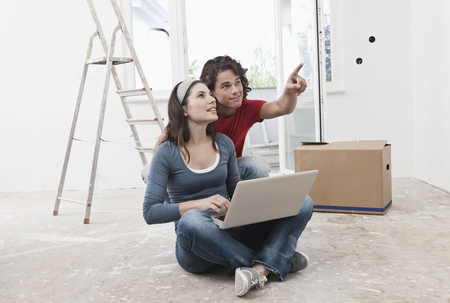 open floor plan: Germany,Cologne,Young Couple Using Laptop And Pointing In Renovating Apartment LANG_EVOIMAGES