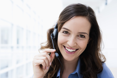Germany,Bavaria,Diessen Am Ammersee,Young Businesswoman Using Headset,Smiling,Portrait LANG_EVOIMAGES
