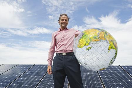 Germany,Munich,Mature Man Holding Globe In Solar Plant,Smiling,Portrait