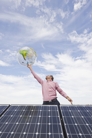 Germany,Munich,Mature Man Balancing Globe On Finger In Solar Plant