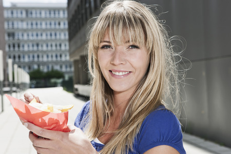 Germany,Cologne,Young Woman Holding French Fries,Smiling,Portrait