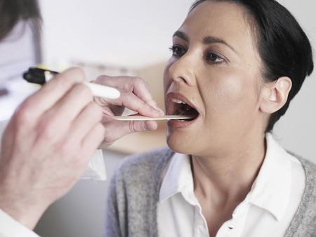 depressor: Germany,Hamburg,Doctor Examining Patient Mouth In Clinic