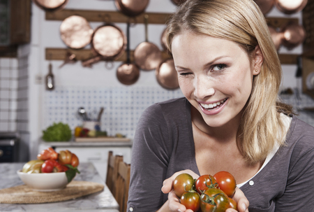 Italy,Tuscany,Magliano,Young Woman Winking And Holding Tomatoes In Kitchen,Smiling,Portrait