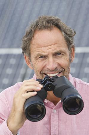 Germany,Munich,Mature Man Holding Binocular In Solar Plant,Smiling,Portrait