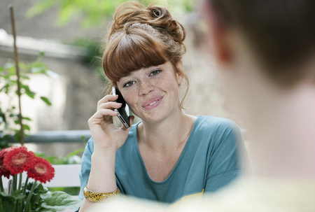 Germany,Berlin,Close Up Of Young Woman Using Cell Phone,Smiling